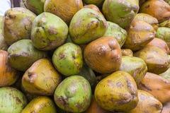 Gröna kokosnötter på en marknadsställning Arkivfoton
