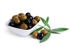 Gröna och svarta oliv i bunken som isoleras på vit Royaltyfri Fotografi