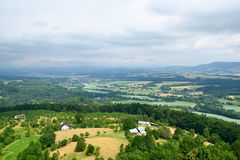 Grüne Landschaft mit Bäumen, Häusern und entfernten Hügeln Lizenzfreie Stockfotos