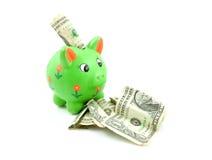 Grüne piggy Querneigung mit Dollar Lizenzfreie Stockbilder