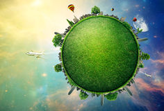 Grüne Planetenerde bedeckt mit Grasstadtskylinen Stockbild