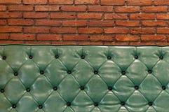 Grüne Retro- Couch in einem Wohnzimmer mit Ziegelsteinwand hinten Stockfotografie