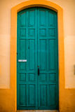 Grüne Tür in der gelben Wand Stockfoto