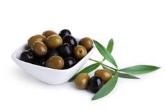 Grüne und schwarze Oliven in der Schüssel lokalisiert auf Weiß Lizenzfreie Stockfotografie