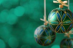 Grüne Weihnachtsbälle, die am abstrakten Hintergrund hängen Stockbilder
