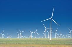 Grüne Wiese mit Windkraftanlagen Stockbilder