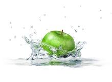 Grüner Apfel, der in Wasser spritzt. Lizenzfreie Stockfotografie