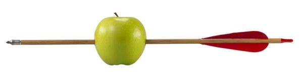Grüner Apfel durchbohrt durch einen Pfeil Lizenzfreie Stockfotos