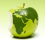 Grüner Apfel mit Erdekarte Stockfotografie