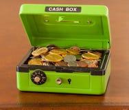 Grüner Bargeldkasten mit den Gold- und Silbermünzen Stockfotografie