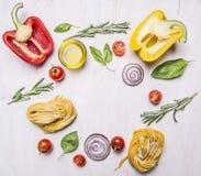 Grüner Pfeffer, Öl, Rosmarin, Kirschtomaten und andere Bestandteile für das Kochen von vegetarischen Teigwaren, zeichneten hölzer Lizenzfreie Stockfotos
