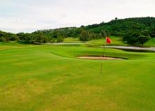Grünes Feld des Golfs mit Zielmarkierungsfahne 1 Stockfotos