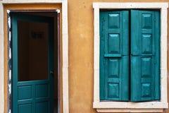 Grünes hölzernes Fenster und Tür auf gelber Wand Stockfotos