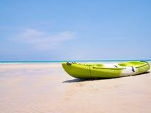 Grünes Kajakboot auf dem tropischen blauen Himmel des Strandhintergrundes und -freien Raumes in Meer Glückliches Sommerferienkonz Lizenzfreies Stockbild