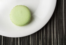 Grünes Macaron auf weißer Platte Stockfotos