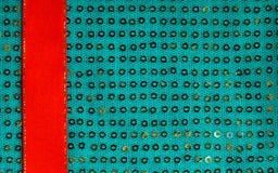 Grünes sequine Hintergrundbeschaffenheitszusammenfassungs-Stoffgewebe und rotes Band Lizenzfreie Stockfotografie