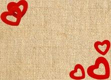 Gränsa ramen av röda hjärtor på säckkanfassäckväv Royaltyfri Fotografi