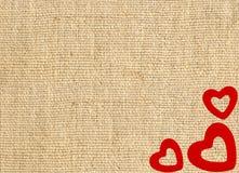 Gränsa ramen av röda hjärtor på säckkanfassäckväv Royaltyfria Bilder