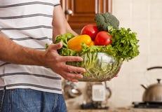 grönsaker för bunkeholdingman Arkivfoton
