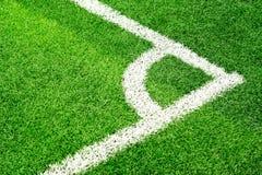 Grönt gräs för fotbollfältet och vithörnet fodrar Arkivfoto