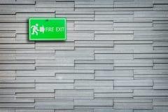 Grönt tecken för brandutgång på stenväggen Fotografering för Bildbyråer