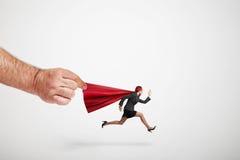 Groß bemannt die Hand, die den roten Mantel des laufenden Superwoman hält lizenzfreie stockfotos