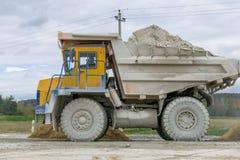 Groß-gelber Steinbruchkipplaster-Erzeugnistransport von Mineralien Stockfoto