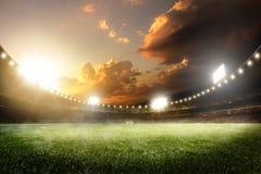 Großartige Fußballarena des leeren Sonnenuntergangs in den Lichtern