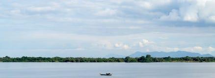 Großartige Seeseiteansicht mit einem einsamen Boot Stockbilder