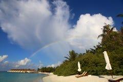 Großartiger Regenbogen auf weißem maledivischem Strand im Himmel mit farbigen Wolken bei Sonnenuntergang stockfoto