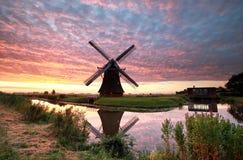 Großartiger Sonnenaufgang über Ackerland mit Windmühle Stockfotografie