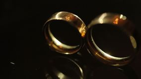 Großaufnahme der goldenen Eheringe, die auf dem dunklen Hintergrund liegen Lichtstrahlen belichten die Ringe stock video footage