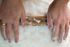 Großaufnahme der Hände mit dem Nudelholz, das den Teig für selbst gemachtes pelmeni bereitstellt Lizenzfreies Stockbild