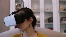 Großaufnahme der jungen Frau in den Gläsern der virtuellen Realität, die zu Hause auf Couch sitzen Weibliches herum schauen im VR stock video