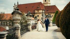 Großaufnahme der netten Jungvermähltenpaare, die entlang die alte barocke Brücke in Prag gehen Lizenzfreie Stockfotografie