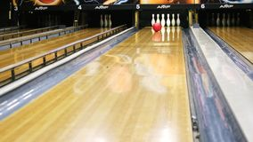 Großaufnahme der Person die Bowlingkugel auf Bowlingbahn werfend und versuchend, Stifte in einem Sportverein unten zu erhalten me stock footage