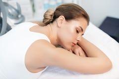 Großaufnahme der schönen jungen ruhigen Frau mit dem natürlichen Make-up, welches auf die Massage beim Lügen im Badekurort wartet lizenzfreies stockbild