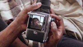 Großaufnahme des afrikanischen Mannes altes photocamera halten, Fotoporträtschönheit nehmend Gemischtrassige Paare auf Bett Stockbild