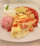 Großaufnahme des Bananenkrepps mit frischer Erdbeere und Erdbeere sauce zusammen mit Erdbeereis- und Peitschencreme lizenzfreie stockbilder