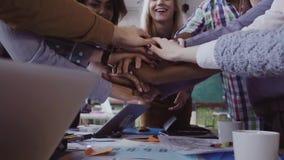 Großaufnahme des jungen Geschäftsteams, das nahe der Tabelle arbeitet, setzt Palme zusammen zwei bemannt die Faust, die sich grüß stock video