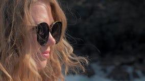 Großaufnahme des jungen Mädchens in der Sonnenbrille, die nahe den Sturmwellen schlagen das junge Mädchen der Felsen heraus schau stock video footage
