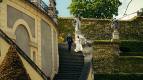 Großaufnahme des netten Jungvermähltenhändchenhaltens beim Hinuntergehen die Treppe Der Altbau wird mit überwältigt Lizenzfreie Stockfotos