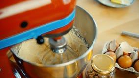 Großaufnahme des roten Mischers den Teig, Bestandteile mischend in der großen Schüssel Konditor, der die Nachtische kocht stock video