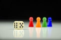 Großaufnahme einer Reihe der bunten Zahlen an der Rückseite mit einem spielenden Würfel auf einem unscharfen weiß-schwarzen Hinte Stockbild