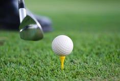 Großaufnahme eines Golfballsatzes auf einem hölzernen Golft-stück im Gras mit einem Golfclub in Position gebracht hinter es als w lizenzfreie stockbilder