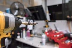 Großaufnahme eines leistungsfähigen elektrischen Werkzeugs gesehen nahe einem Werktisch und einer Werkzeugausstattung lizenzfreie stockbilder
