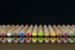 Großaufnahme eines Satzes farbiger Bleistifte, die auf einer Glasmatte mit Reflexion liegen Stockbild