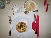 Großaufnahme eines Tasse Kaffees mit Zucker und einer Platte des Nachtischs mit einer Scheibe des Kuchens stehend auf einer Umhül lizenzfreie stockfotos