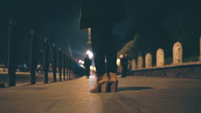 Großaufnahme von den weiblichen Beinen, die Schuhe auf einem hohen Absatz tragen Frau, die auf der Brücke steht, am Abend und an  Stockfoto