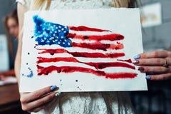 Großaufnahme von den weiblichen Händen, die ein Blatt Papier mit einer hand--darwn Aquarellillustration der Flagge von halten Stockbild